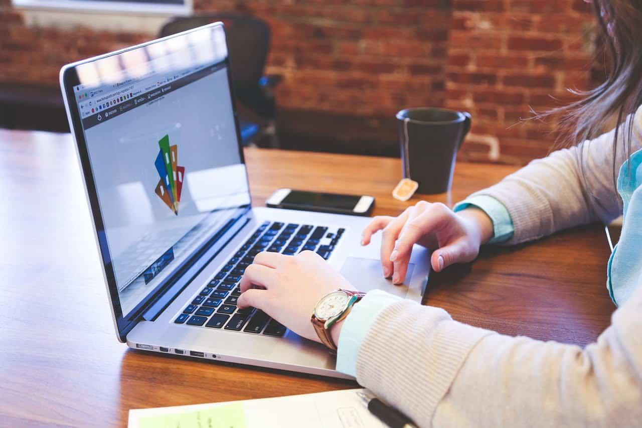 Kuva suunnittelijasta kannettavan tietokoneen äärellä teekupposen kanssa.